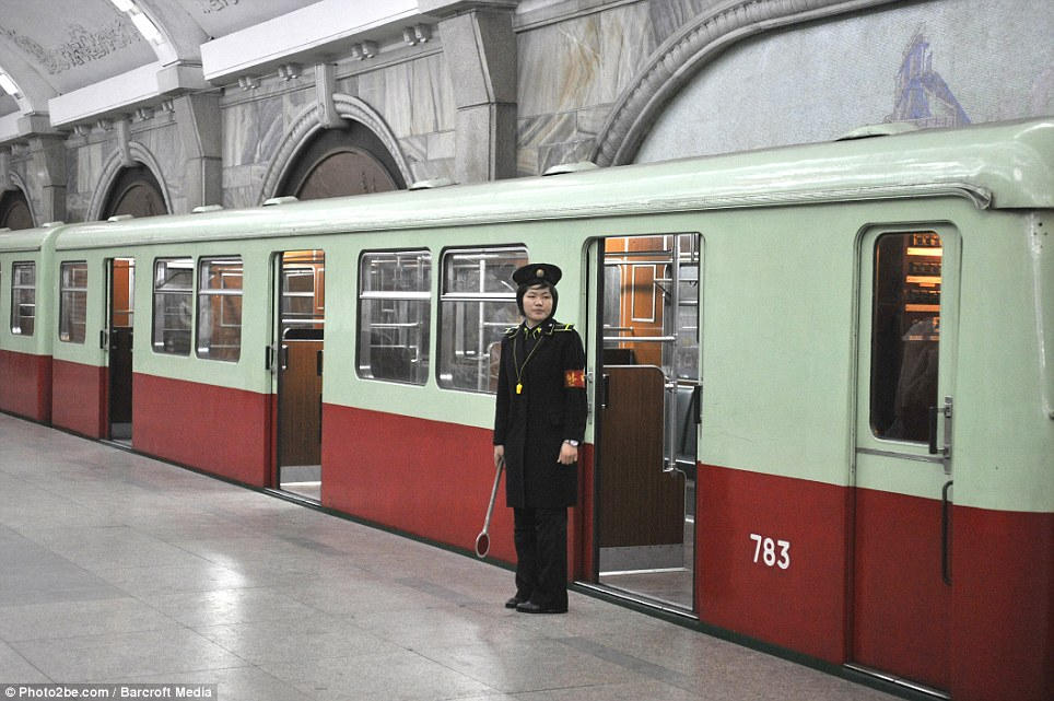 Cut off the outside world: A female train hostess stands outside a carriage at the Pyongyang subway, which is also used as a nuclear shelter