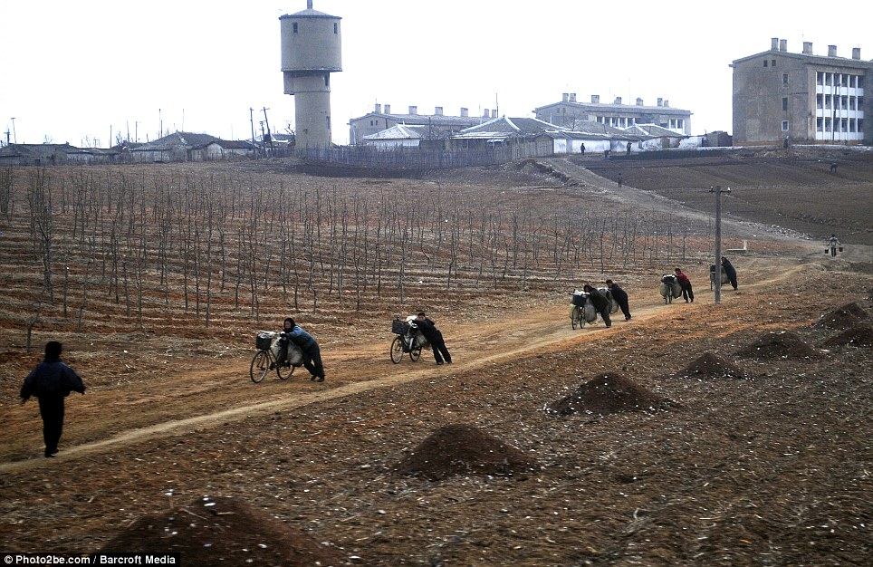 True view: Women pictured transporting material to farmers in North Korea, which attempts to hide the poverty and deprivation from the outside world