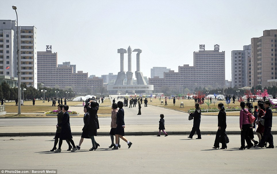 Secretive state: North Koreans walk past the country's symbol of art in the capital Pyongyang