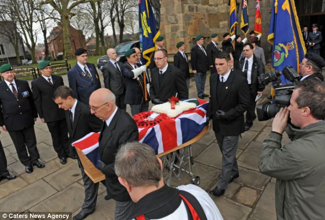 Final send off: Mr Vaughan's coffin leaves the church watched by standard bearers and members of the public