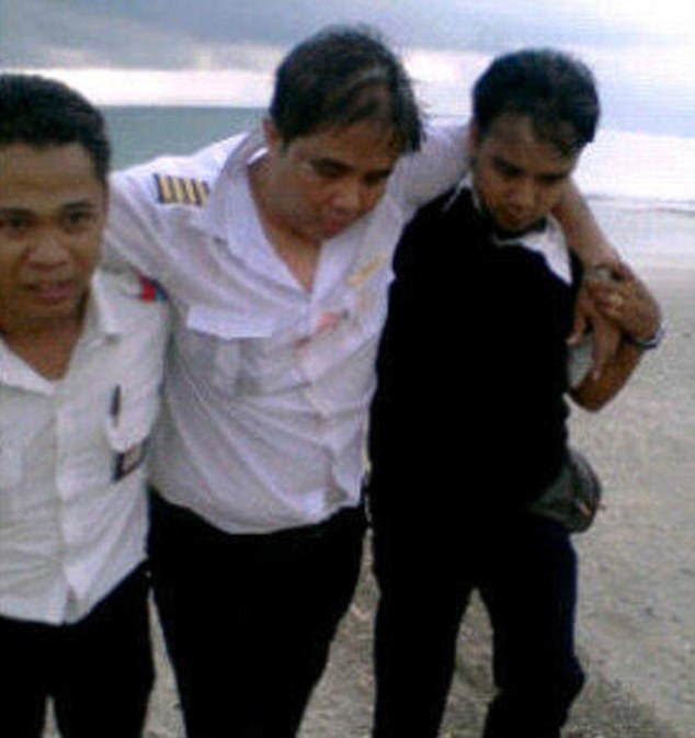 Injured: Lion Airways Pilot M.Ghazali is pictured being helped ashore following the crash