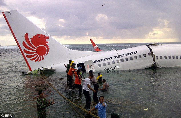 Close call: These passengers balanced precariously on the aircraft's wing as it began to sink under the water