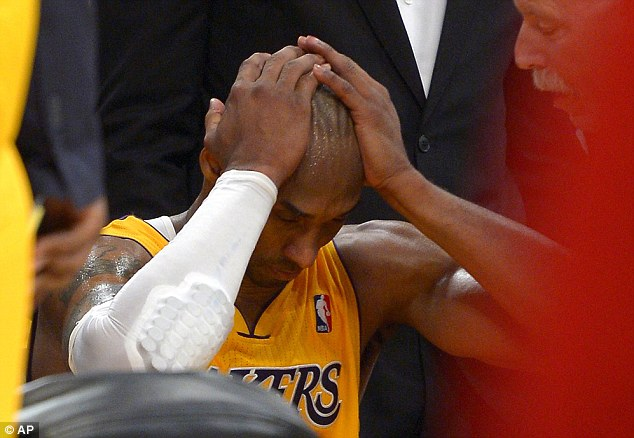 Benched: Bryant puts his head in his hands as head coach Mike D'Antoni leans over him