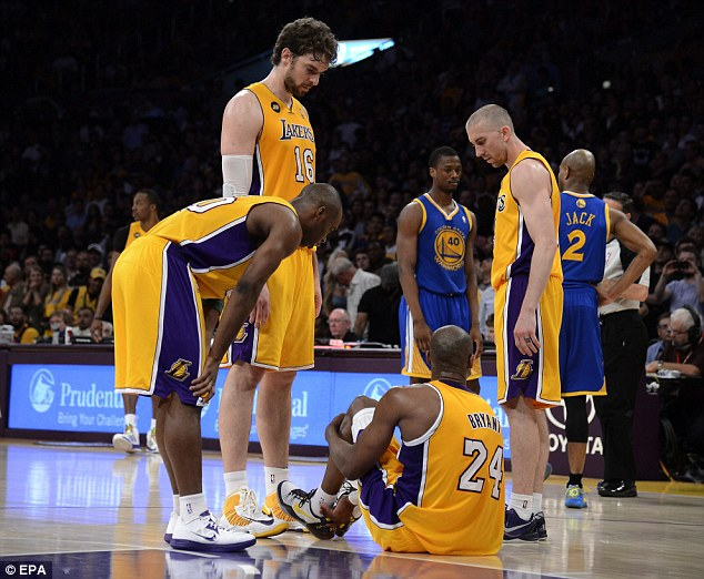 Support: Teammates Pau Gasol (second left), Jodie Meeks (left), and Steve Blake (right) stand around Bryant before helping him walk off the court