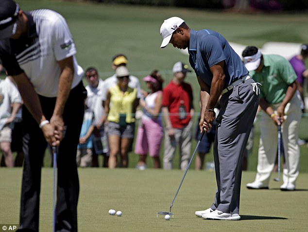 Round three: Woods, right, is seen putting on the practice green before the third round on Saturday afternoon after assessed a 2-stroke penalty by the rules committee for the drop on Friday
