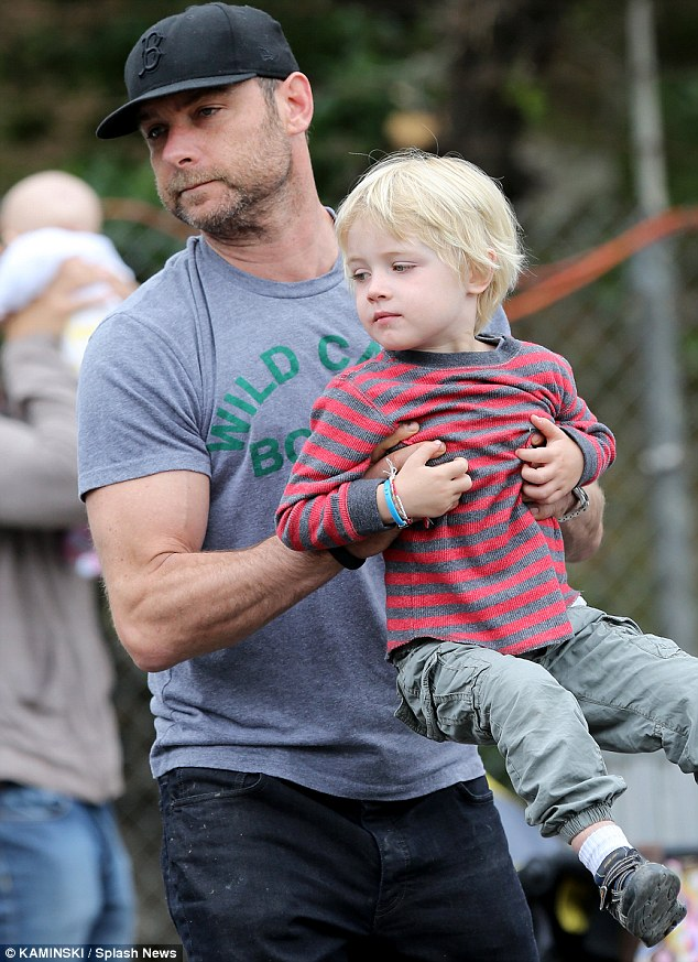 Fit father: The 45-year-old actor's arm muscles bulged as he hoisted his younger son into the air