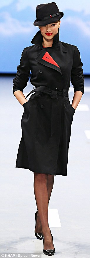 Super chic flying attire: Miranda also paraded an equally chic navy trench coat featuring red lining, and a classy fedora hat
