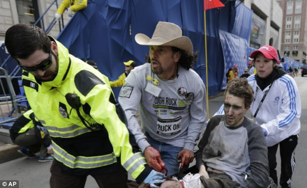 Costa Rican immigrant Carlos Arredondo helps medical workers run an injured man past the finish line the 2013 Boston Marathon