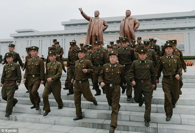 Show of force: Soldiers visit Mansu Hill in Pyongyang, where bronze statues (in the background) of former North Korean leaders Kim Il Sung and Kim Jong Il stand as the country celebrated the birth of its founder