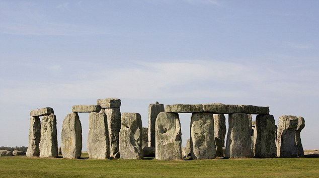 Monument: The three huts being built are similar to those which were used to house  workers who built the famous Stonehenge