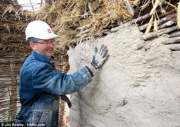 Tough job: A volunteer works on a wall at one of the neolithic house recreations