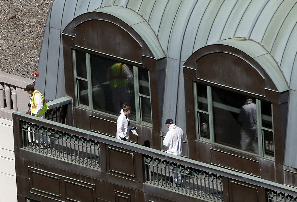 Forensic investigators look through the top of a building on Boylston Street for clues, two days after the bombs exploded just before the Boston Marathon finish line