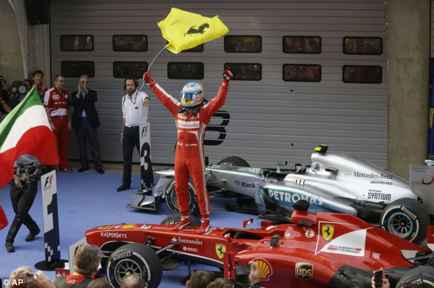 Paying off: Ferrari driver Fernando Alonso of Spain stands on his car and waves a flag as he celebrates his win at the Chinese Formula One Grand Prix