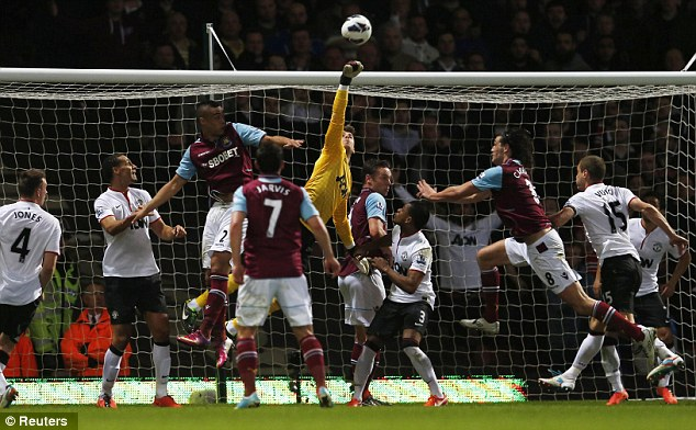 Collision course: Andy Carroll and David de Gea came together from a corner in the first half
