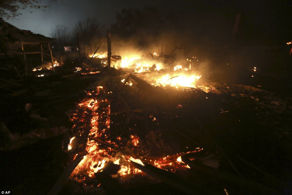 Remains: A destroyed home burns early Thursday morning as rescue teams search for victims and go from door-to-door to check on residents who could have been hurt