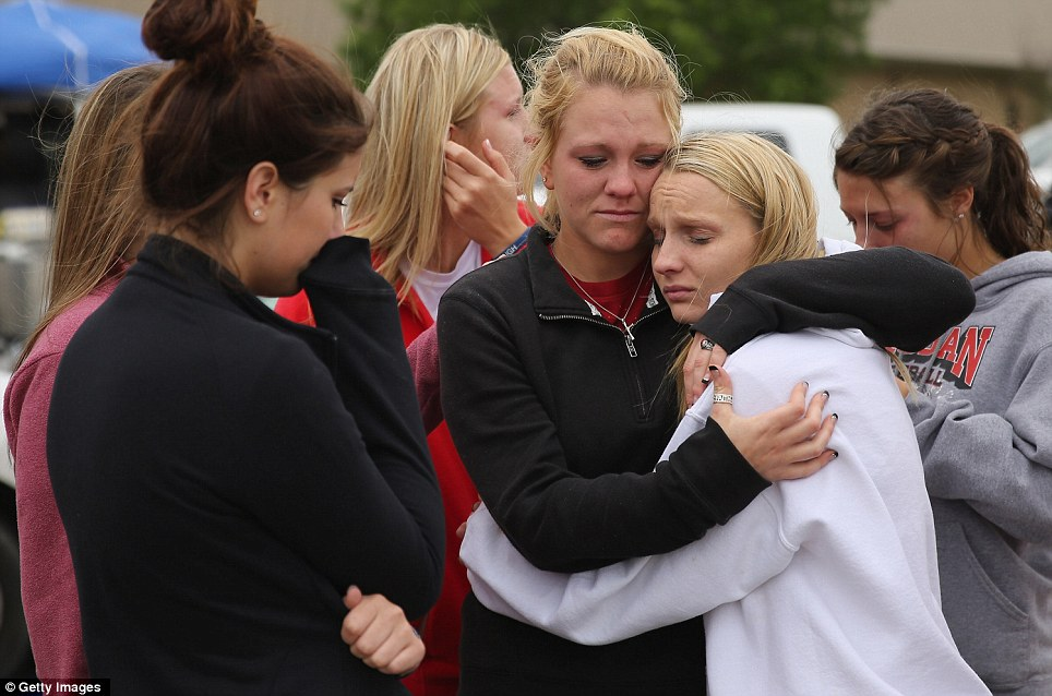 Grief: West High School senior students Kelsey Hoelscher (center) and Heather Perry (right) embrace after praying for the victims and survivors of the blast