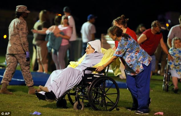 Emergency workers help an elderly person to safety at a school stadium in West