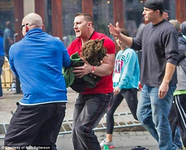 Heroic: Matt Patterson, center, an off-duty firefighter, and Michael Chase, left, a trained police officer who works with troubled youths, ran the boy, in Patterson's arms, a full block and a half to medical teams