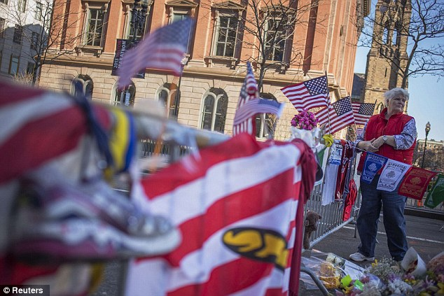 Aftermath: A woman stands by a makeshift memorial for the victims of the Boston Marathon bombings on Boylston street in Boston, Massachusetts April 18, 2013