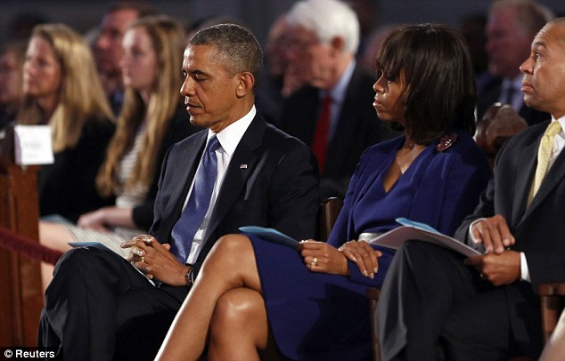 Together: The president and first lady listen before he takes to the podium to honor victims at the service