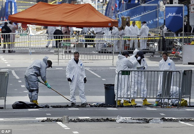 Investigation: People in protective suits rake and examine material on Boylston Street in Boston on Thursday as the investigation into the bombing continues