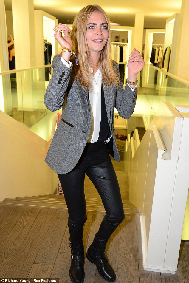 Interesting moves: Cara Delevingne shows off her bad moves as she attends the Taken By Storm photography exhibition on Wednesday night