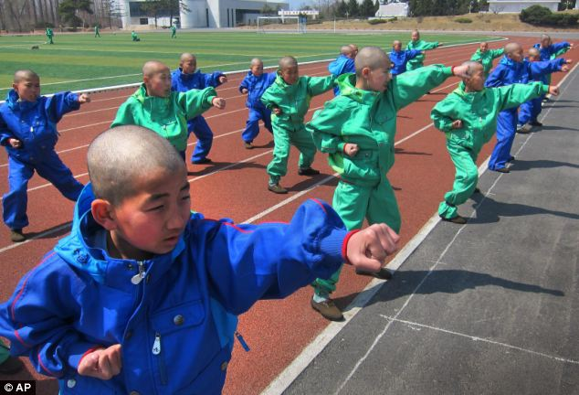 Young children with shaven heads learn taekwondo at the Mangyongdae Revolutionary School where former leader Kim Jong Il once studied