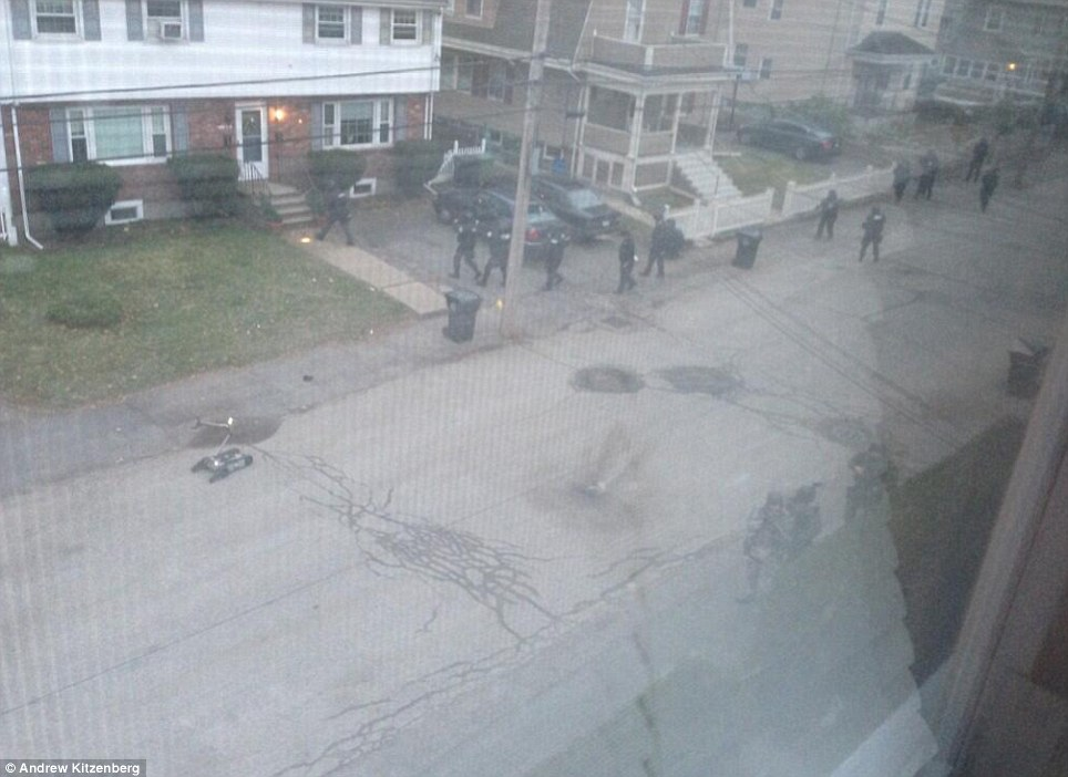 Swarming the streets: Dozens of armed officers check houses in the suburb of Watertown after the second suspect fled during a car chase and firefight