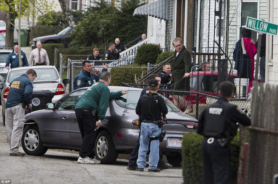 Cautious:  Police from several different agencies search an apartment complex after a shootout