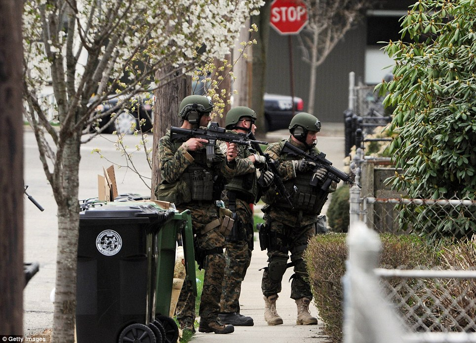 Volatile: Police conduct a door-to-door search for 19-year-old Boston Marathon bombing suspect Dzhokhar Tsarnaev after it emerged that IEDs had been found at two addresses in Watertown and Cambridge
