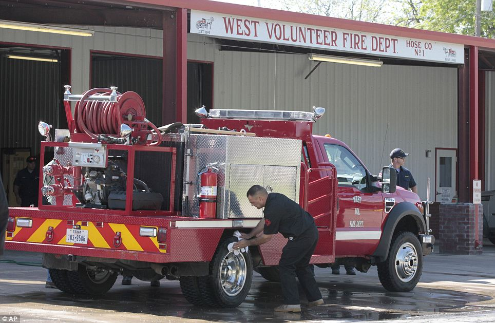 Sacrifice: Texas volunteer firefighters clean a fire unit at their headquarters on Friday.