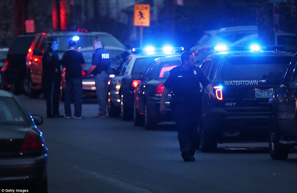 Cornered: Police converge near the scene where it was believed 19-year-old bombing suspect Dzhokhar Tsarnaev is in hiding