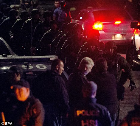 An ambulance carries Boston Marathon bombing suspect Dzhokhar Tsarnaev from the scene after he was apprehended in Watertown, Massachusetts, USA on Friday (left) as Police SWAT teams leave the area (right)