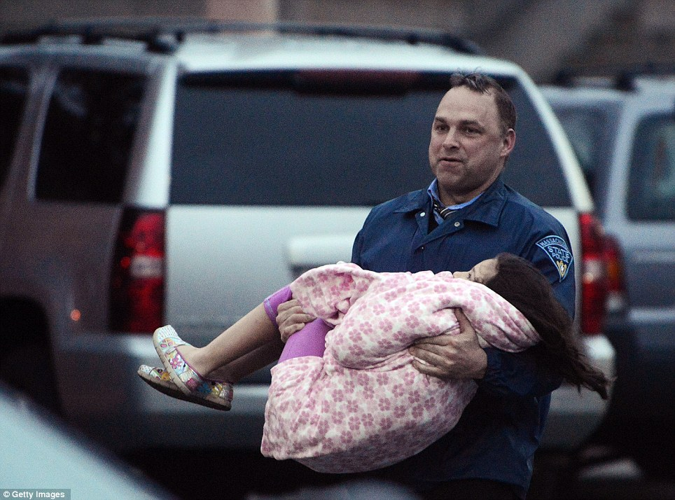 An officer carries a child away from an area where a suspect is hiding on Franklin St., on April 19, 2013 in Watertown, Massachusetts