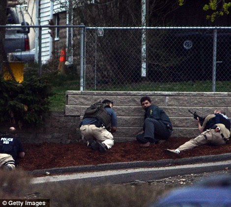 Residents flee from an area where a suspect is hiding on Franklin St., on April 19, 2013 in Watertown, Massachusetts as law enforcement position themselves