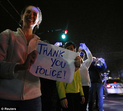 Members of the public cheer as police officers leave the scene where Dzhokhar Tsarnaev, the surviving suspect in the Boston Marathon bombings, was taken into custody in Watertown, Massachusetts on Friday