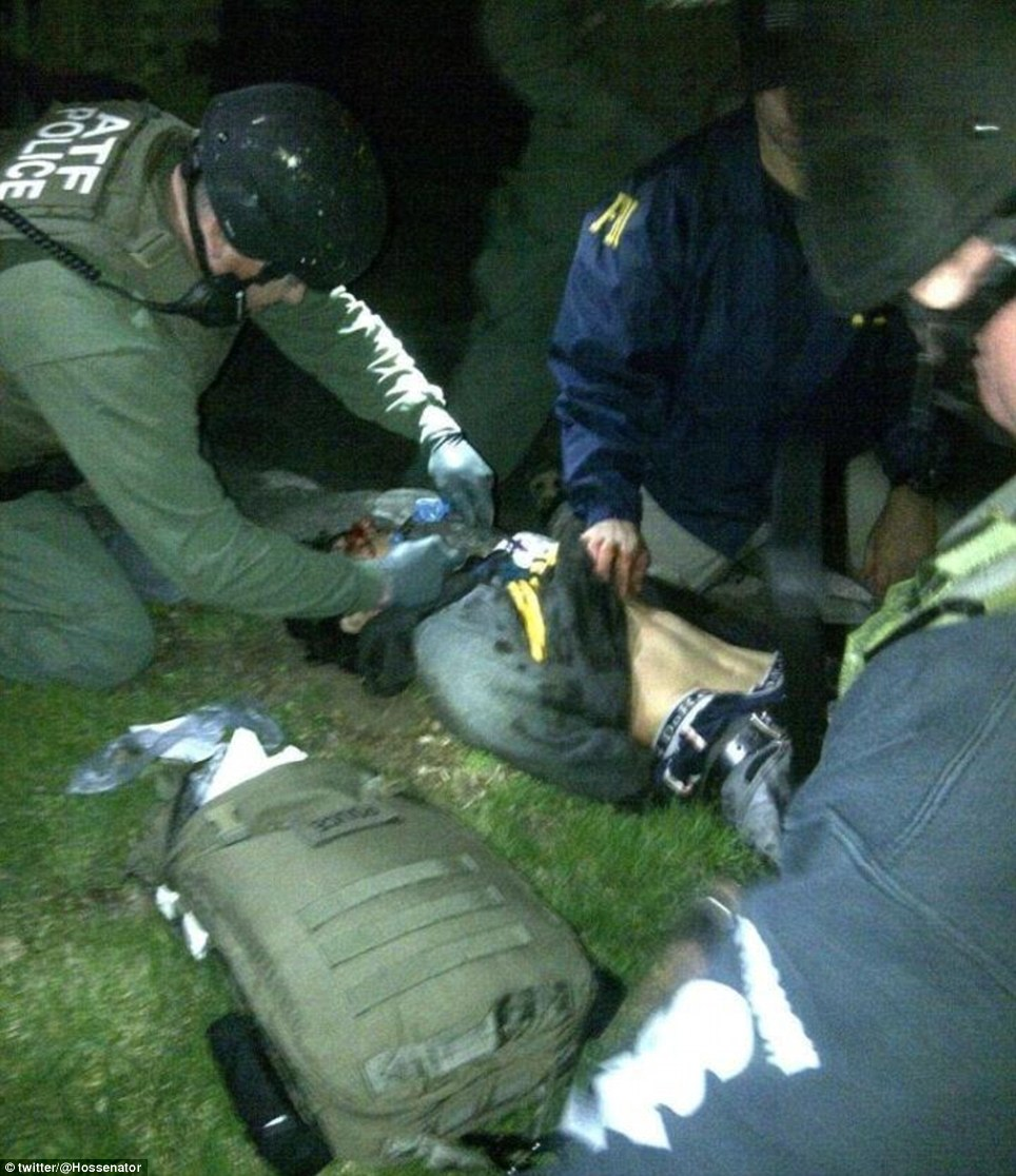 Assisted: This striking picture shows Dzhokhar Tsarnaev lying on the ground of the property of 67 Franklin Street in Watertown after authorities apprehended him. He had to have medical assistance to breathe