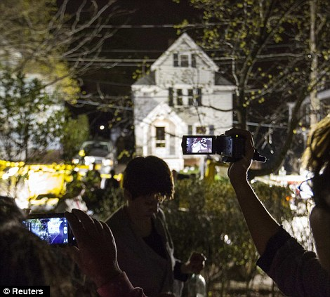 Neighbors use cameras to record images of the boat at 67 Franklin St. where Dzhokhar Tsarnaev, the surviving suspect in the Boston Marathon bombings, was hiding inside in Watertown, Massachusetts on Friday