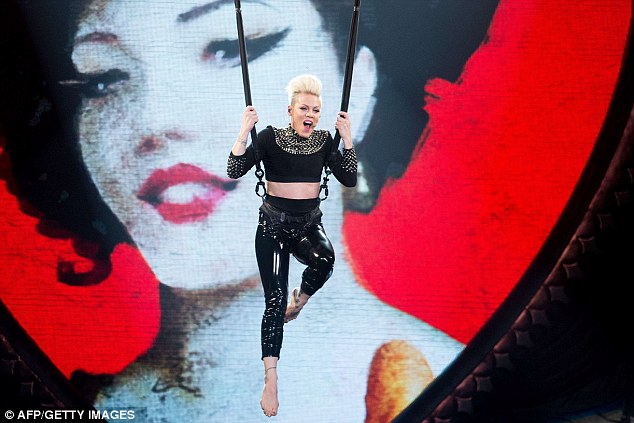 Flying high: She flew high above the crowds as she was hoisted up in her black PVC outfit