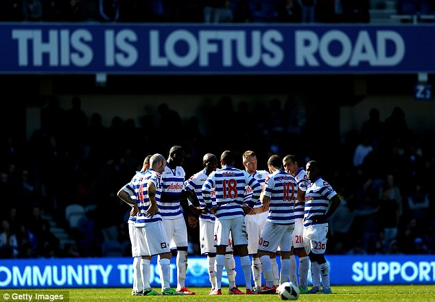 Work to do: QPR players formed a huddle at the start of the second half when they trailed 1-0