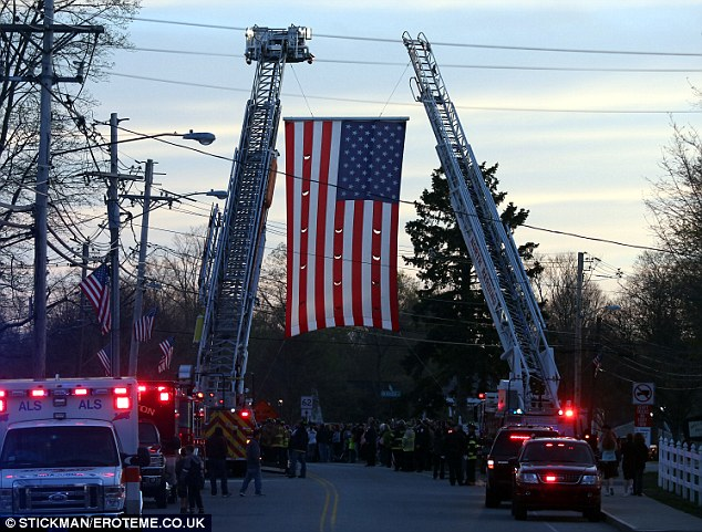 Standing tall: Two fire trucks raised their ladders to support a giant American flag Collier's hearse passed under