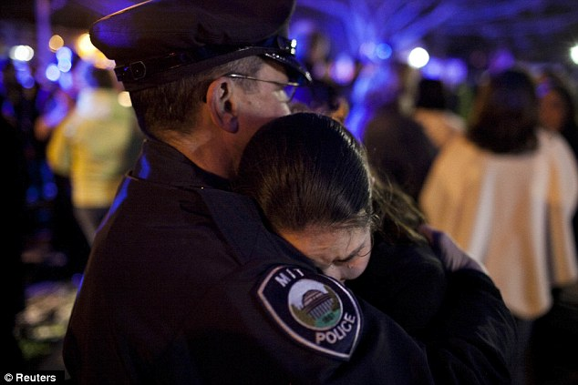 Prayers: A woman hugs an MIT police officer after the vigil with the family now sending their thoughts and prayers to the other MBTA police officer seriously injured, Richard Donohue Jr