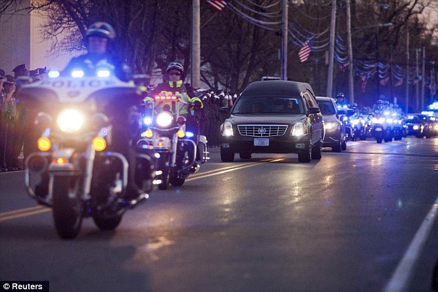 Final farewell: A hearse transporting the body of slain MIT police officer Sean Collier drives down Church Street near the Town Common in Wilmington