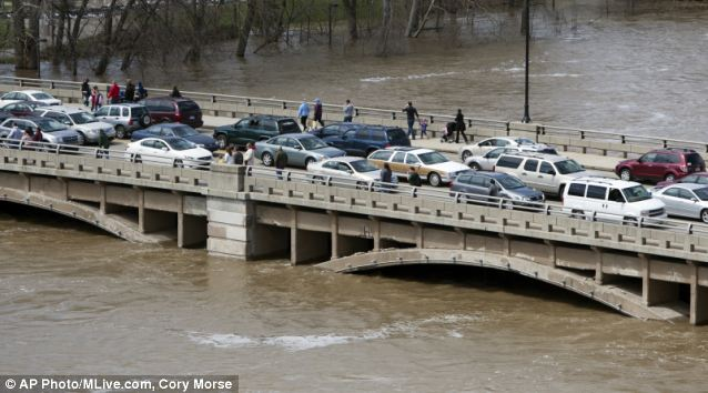 Depth: Traffic clogs the Pearl Street bridge as crowds of people check out the level of the swollen river in downtown Grand Rapids. The river hit a record 21.86ft yesterday morning