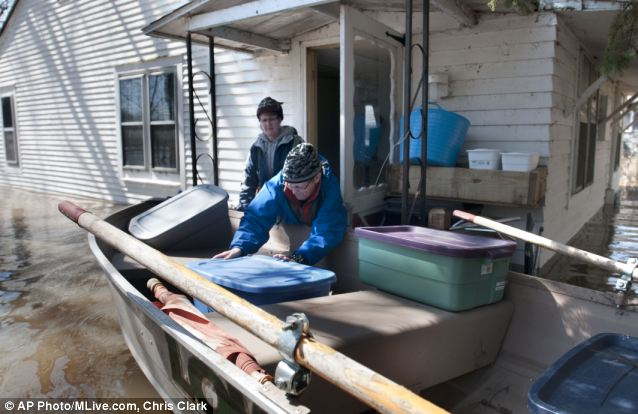 Escape: Kate Krueger removes belongings from the flooded home she rents on the Grand River north of downtown Grand Rapids. She is helped by her friend Wendy Kondracki