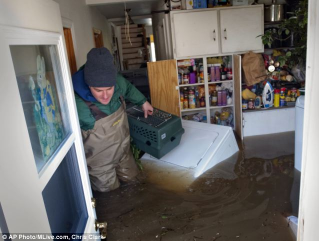 Misery: Mr Biggerstaff wades past a floating clothes dryer in his mother's home. The flooded river has caused misery over a large swathe of Michigan