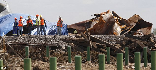 Workers are pictured among the debris of the plant. The cause of the explosion has still not been determined