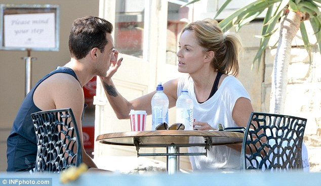 Affectionate: The TV star was seen rubbing something off the 23-year-old's face while they sat in the sun