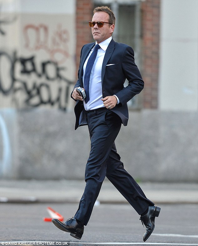 On the go: Kiefer sported a blue suit as he rushed across the street in the East Village