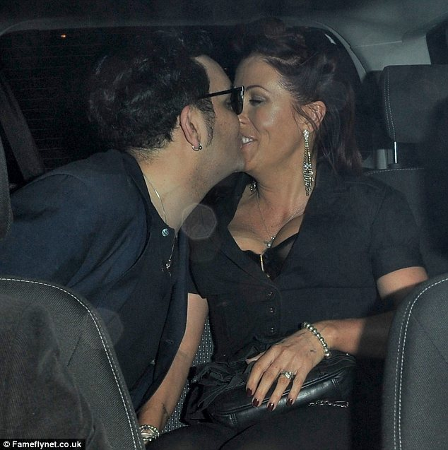 All loved up: Jessie Wallace and her boyfriend Tim Arnold were seen smooching in the back of a car after a night out in London